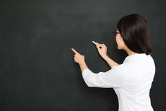 A good asian teacher writing question on blackboard with chalk. A good asian teacher writing on blackboard with chalk in classroom stock images