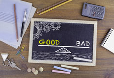 Good and Bad Balance. Chalkboard on wooden office desk Royalty Free Stock Image
