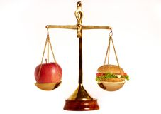 Good and bad diet. Apple and hamburger on a weight scales as concept for good and bad diet Royalty Free Stock Image