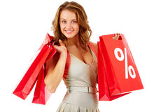 Good bargain. Portrait of a girl holding handbags with discount symbol, looking at camera and smiling Royalty Free Stock Photos