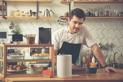 Good barista booking preferences of customer. Kind handsome man typing order of visitor on digital tablet. He standing near shelf with tasty cakes Royalty Free Stock Images