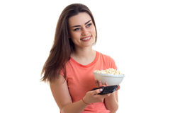 Good beautiful girl with remote control in her hand and a plate pop corn close-up. Isolated on white background Stock Photography