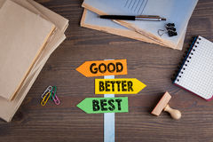 Good, better and best concept. Paper signpost on a wooden desk stock photography