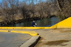 A Good Book by the Roanoke River. Roanoke, VA – January 7th: A gentleman sitting the low water bridge and reading a good book by the Roanoke River located royalty free stock photo