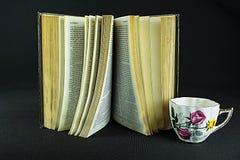 A good book. An book and tea cup on a black back ground Stock Photos
