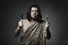 Good breeding. Hungry wild man wearing leopard skin hold fork and knife Stock Photos