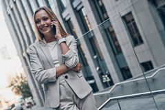 Good business talk. Beautiful young woman in suit talking on the phone and smiling while standing outdoors royalty free stock image