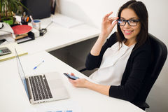 Good business talk. Cheerful young beautiful woman in glasses talking on mobile phone and using laptop with smile while Royalty Free Stock Photography