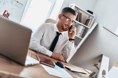 Good business talk. Handsome young man in formalwear talking on the phone and smiling while sitting in the office stock photography