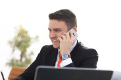 Good business talk. Handsome young man in formalwear talking on the phone and smiling while sitting. At the office desk Stock Image