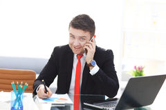 Good business talk. Handsome young man in formalwear talking on the phone and smiling while sitting. At the office desk Royalty Free Stock Photos