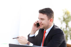 Good business talk. Handsome young man in formalwear talking on the phone and smiling while sitting. At the office desk Royalty Free Stock Images