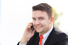 Good business talk. Handsome young man in formalwear talking on the phone and smiling while sitting. At the office desk Stock Images