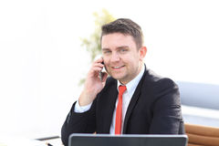 Good business talk. Handsome young man in formalwear talking on the phone and smiling while sitting. At the office desk Royalty Free Stock Image