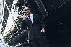 Good business talk. Handsome young man in full suit talking on the phone and smiling while standing outdoors royalty free stock photo