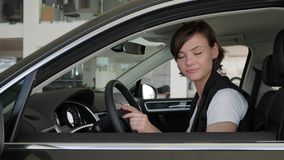 Good buy, admiration from novel machine, Portrait owner new. Automobile, driver inspects auto, Happy woman client sitting in vehicle, customer considering new stock video footage