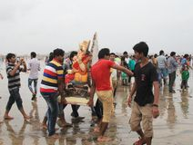 Good bye god. Devotees take out procession of lord Ganesh in the Religious festival of Ganesha immersion in sea water in India Royalty Free Stock Images