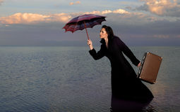 Good-bye Mary. The beautiful girl in a black coat with an umbrella and a suitcase costs in water Stock Photography