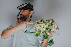 Man with beard in swimming mask is holding cauliflower. Good catch. A contented man in a swimming mask holds in his hand cauliflowers like coral. Comic story stock photos