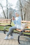 Inspired woman drinking coffee while sitting on the bench. Good coffee. Joyful blond woman drinking coffee while sitting on the bench Royalty Free Stock Photo
