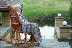 An elderly woman sits in a wicker rocking chair and talking on a cell phone.Good communication.Relax in a country house. royalty free stock photo
