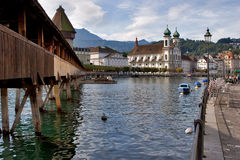 Good day. Lucerne lake quay with wooden bridge and a church Stock Photography