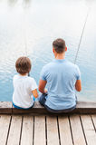 Good day for fishing. Rear view of father and son fishing while sitting on quayside together Royalty Free Stock Images