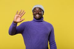 Emotional dark-skinned man demonstrating his perfect smile. Good day. Handsome model standing over yellow background and expressing positivity royalty free stock photo