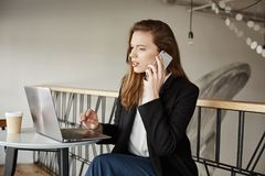 Good day I want to submit internet order. Portrait of good-looking busy woman sitting in cafe, making reservation in Stock Photo