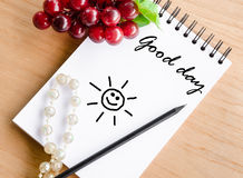 Good day wording on white diary and red grape Stock Images