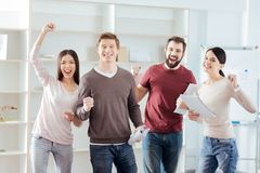 Charming four colleagues celebrating victory. Good deal. Pretty merry four colleagues demonstrating happiness  while  standing and staring at the camera Royalty Free Stock Photo