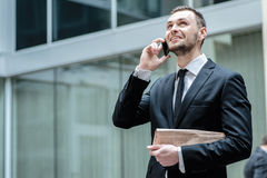 A good deal! Young businessman speaks by phone and laughs. Stock Images