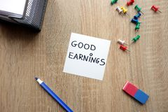 Good earnings concept. With message on wooden table stock image