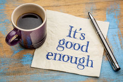 It is good enough concept. It is good enough - efficiency and productivity concept - handwriting on a napkin with a cup of espresso coffee stock photography