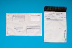 Russian post polyethylene envelope on blue background. Plastic Postal Mailing Bags royalty free stock photos