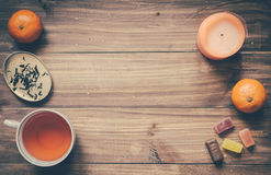 Good Evening Concept. Sweets, mandarins, cup of tea and other elements on wooden table Royalty Free Stock Photos
