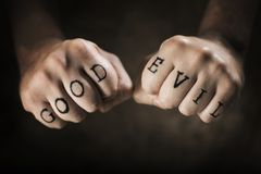Good or Evil. Man with Good and Evil fake tattoos royalty free stock image