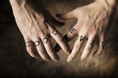 Good or Evil. Man with Good and Evil (fake) tattoos on his hands stock photo