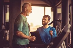 Good exercise. Jogging. Personal trainer giving support senior men during exercise stock images