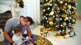 Good Father And Little Girl Spend Time And Holding Gadget Sitting on Floor in Large Room on Background of Decorated. Cheerful Handsome Male Baby Girl Dad Helps stock video footage