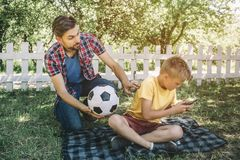 Good father is looking at his son and holding a ball. He wants to play with his son. Child is playing on phone. He doesn. `t want to play football stock photography
