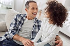 Alert father talking with his daughter. Good father. Good-looking inspired dark-haired men smiling and talking with his daughter and they looking at each other Royalty Free Stock Image