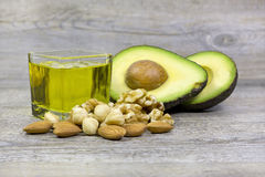 Good fats examples. Group of good fats food examples olive oil, dry fruits and avocado on a wooden surface Stock Photos