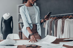 Good feedback from client. Close-up of young African woman holding a smart phone and smiling while standing in her studio near the clothes hanging on the racks Royalty Free Stock Photos