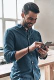 Good feedback from client. Handsome young man using smart phone and smiling while standing in the office Royalty Free Stock Photography