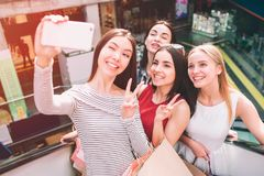 Good female company is standing together on escalator and taking selfie. They are looking at phone and smiling. Asian. Girl is holding phone stock image