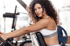 Good fit curly girl dressed in sports clothes is doing exercise on the sports equipment in the modern gym full of sun royalty free stock photos