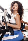 Good fit curly girl dressed in sports clothes is doing exercise on the sports equipment in the modern gym full of sun royalty free stock images