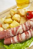 Good food. Sausages with bacon & fried potatos Royalty Free Stock Photos
