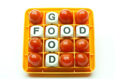 Good Food Cherry Tomatoes. The words Good Food are formed by letters in a puzzle game and surrounded by nine cherry tomatoes Stock Images